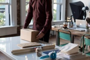 A man packing up a box on a counter.