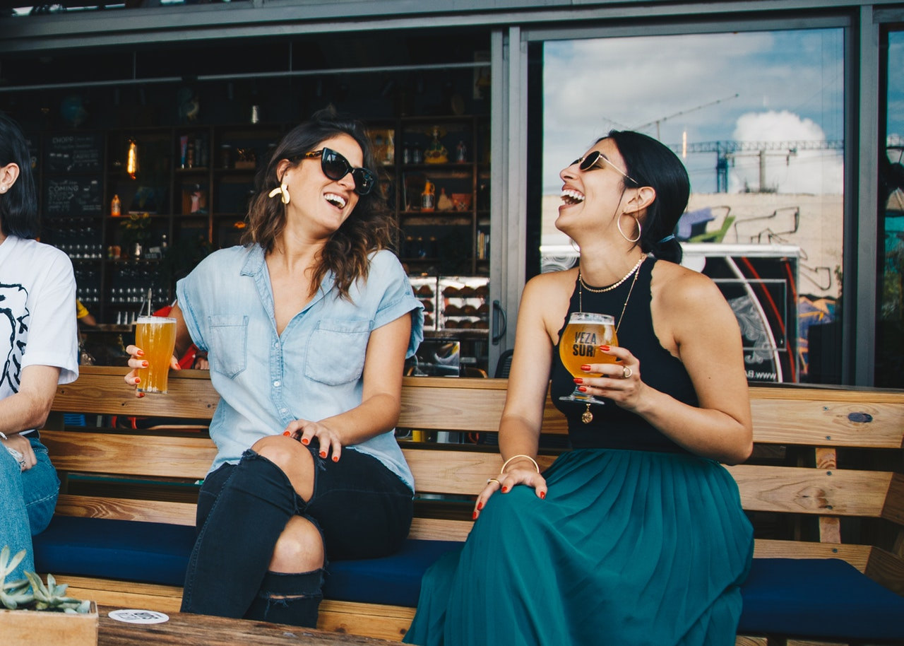 Two women sitting on a bench, laughing and holding glasses of beer.