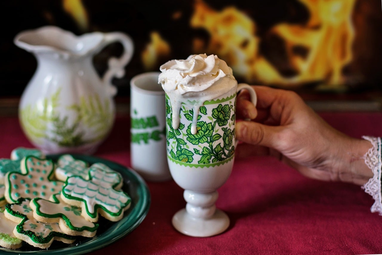 A mug of coffee topped with whip cream next to a plate of cookies.