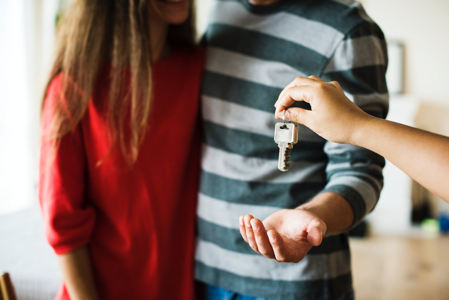 A couple being handed the keys to a home.