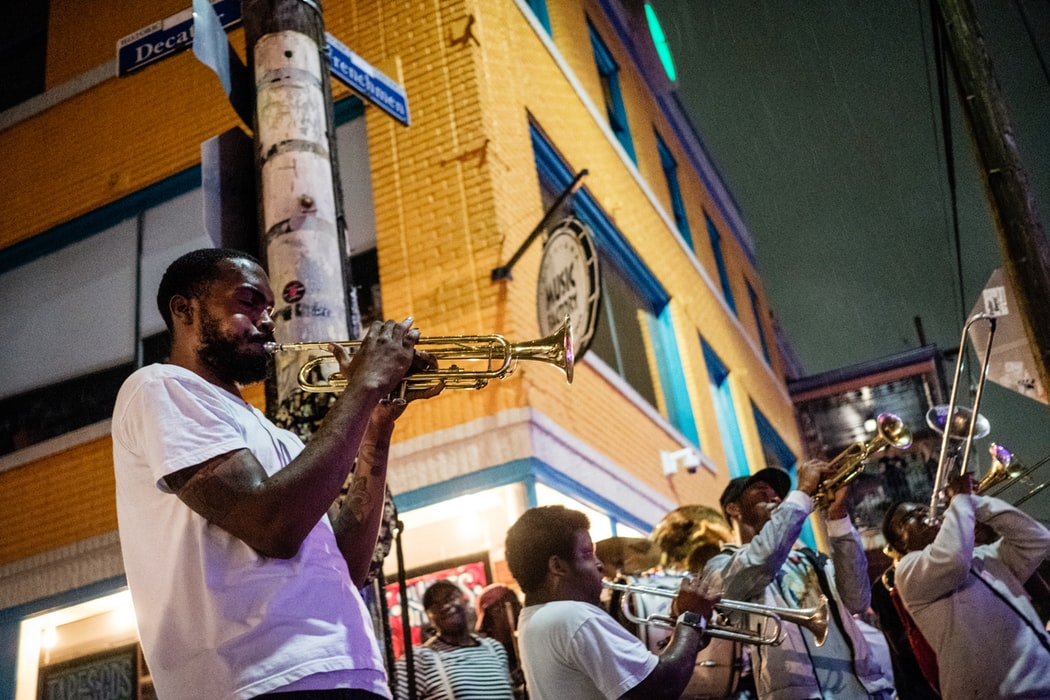 Men playing trumpet on the street.